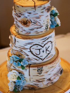 Rustic carved birch wedding cake. Hand painted with sugar flowers. Photo Copyright Wildflour Cake Design