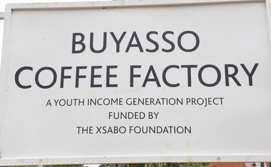 """Signpost """"Buyasso Coffee Factory,"""" an income generation initiative of The Xsabo Foundation for the youth."""