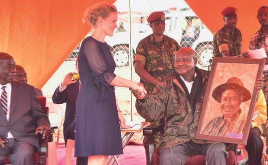 Franziska Leischker presents a gift of the team (portrait out of banana fibres by Joseph Tamale Ssekiziyivu) to President Yoweri K. Museveni.
