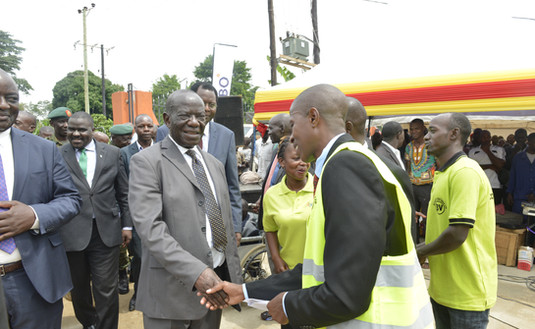 Robert Kasagga, Project Manager, construction of the coffee factory for the youth, greets Vice President Edward K. Ssekandi.