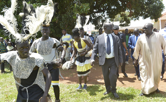 Vice President Edward K. Ssekandi (in suit), HRH Chief Richard S. Apire and Justice Ralph Ochan, Chairman of the Public Service Commission (behind the Chief) join traditional dancers after touring the Mobile Medical Camp in Atiak Township that was sponsored by The Xsabo Foundation.