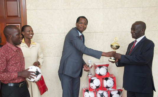 Dr. Alobo, CEO/Managing Director of The Xsabo Group, hands over a donation by The Xsabo Foundation of trophies and 96 footballs, including original FC Bayern Munich and UEFA Champions League balls, to Vice President Ssekandi in support of the VP's youth sports initiative.