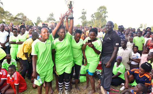 A women's football team in Greater Masaka with Xsabo tricots display the cup they just won.