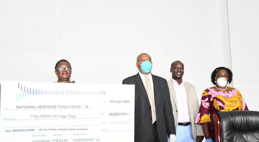 Uganda's Prime Minister Dr. Ruhakana Rugunda, who is also Chairman of the National Task Force on COVID-19, second left, receives The Xsabo Foundation's donation of UGX 50 million from Frances Ruth Atala (left), A Director of The Xsabo Foundation, in the presence of Mary Karooro Okurut, Minister (General Duties) in the Office of the Prime Minister (right).