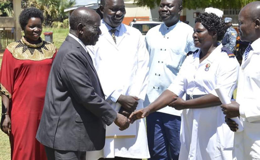 (Left to right): Agnes Linda Auma (Resident District Commissioner Amuru) and the District Medical Officer and his team welcome Uganda's Vice President Ssekandi to the Mobile Medical Camp in Atiak.
