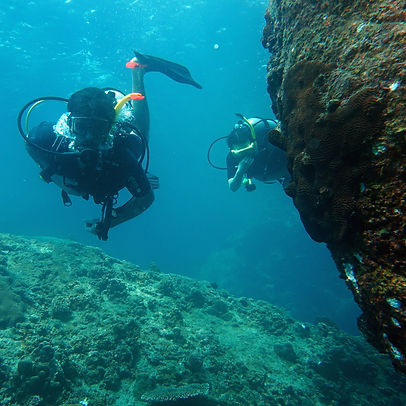 Two scuba divers rounding a rock in koh Tao