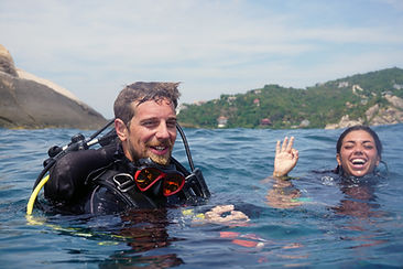 A Scuba diving instructor with a student on the surface