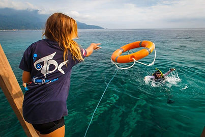 A Rescue diver student throwing a boyancy device to a diver in distress