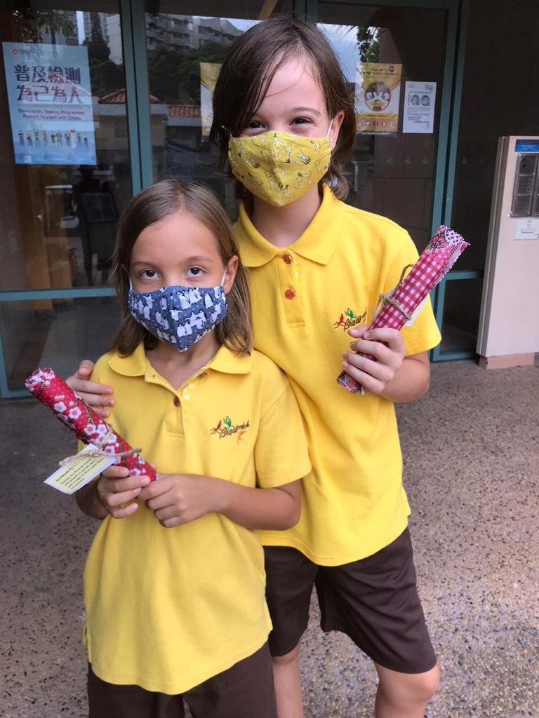 Two Hong Kong Brownies wearing cloth masks and holding homemade beeswax wraps