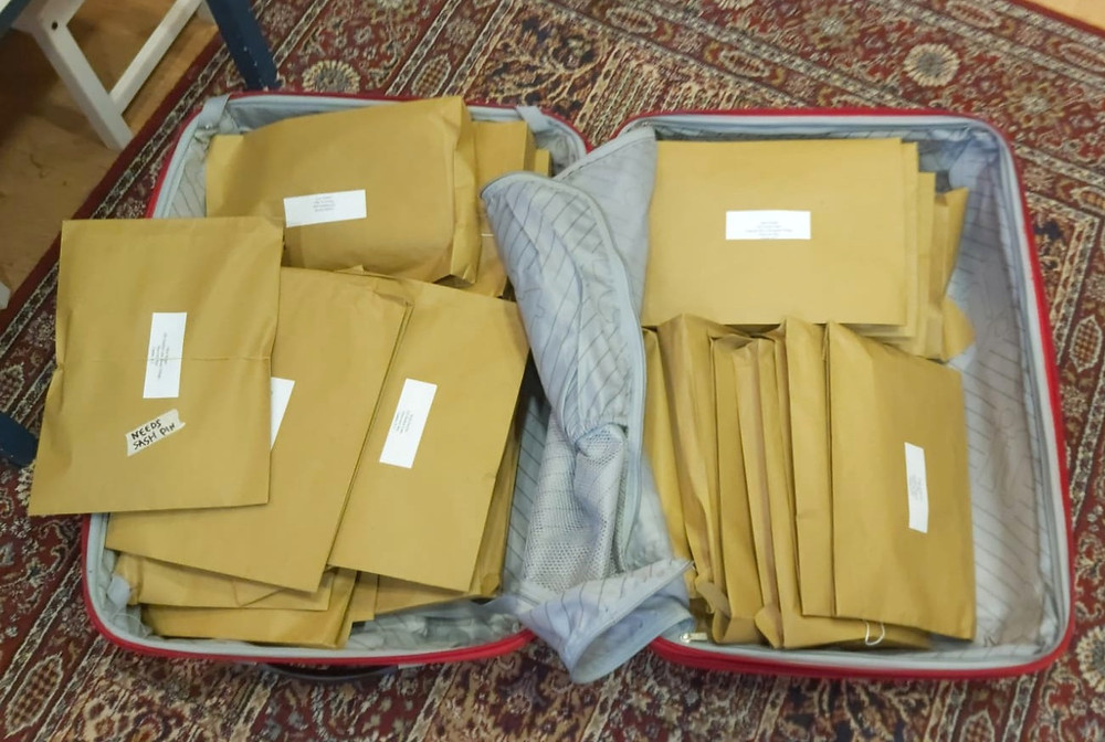 Brown paper envelopes in an open suitcase with grey lining on a red patterned rug