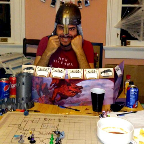 Man in medieval attire smiling behind his GM screen as he referees a Dungeons and Dragons campaign
