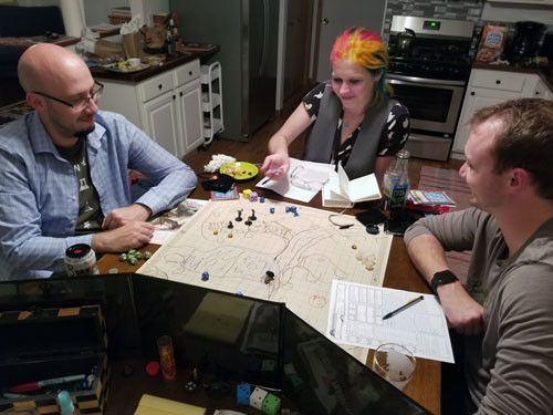 A woman rolling dice with two men during a Dungeons and Dragons tabletop RPG