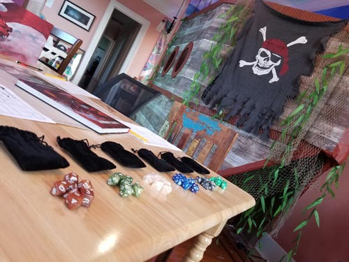 Pirate ship handmade by Zero Session standing behind a tabletop rpg setup with dice for game night