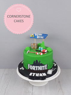 "Shown as a fondant finished standard height 7"" cake - feeds 15. Complete with Victory Royale banner, trunk, pick axe, energy packs, first aid kit and bandages. Personalised with name and age on dog tag."