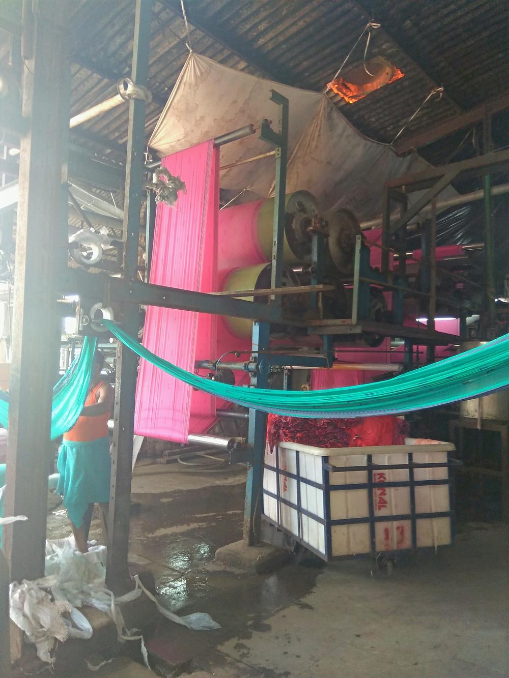 עובד במכנסים קצרים וכפכפים לצד חומרים מסוכנים במפעל טקסטיל בהודו