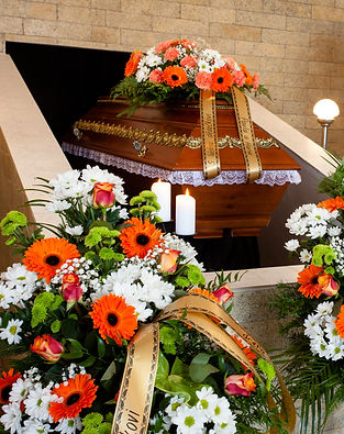 Funeral hall with wooden coffin and flow