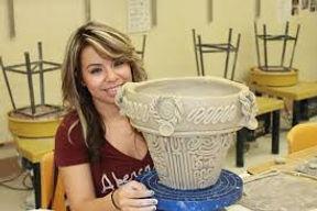 Handbuilding a coil pot in pottery class