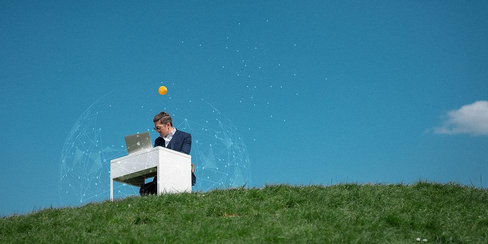 Patrick Kappeler an einem Schreibtisch auf einer grünen Wiese