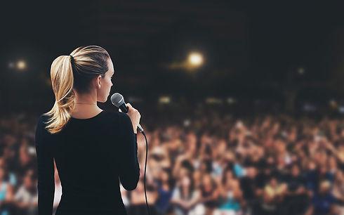 Frau hält einen Vortrag vor Publikum