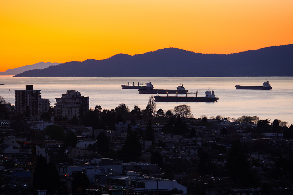 Sunset view from Arras Vancouver overlooking Vancouver Harbour with anchored freighters in front of the North Shore Mountains in the background.