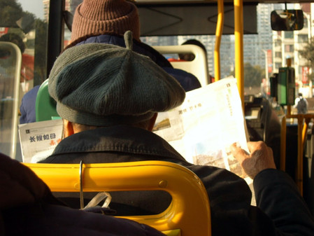 Man reading on the bus, China.