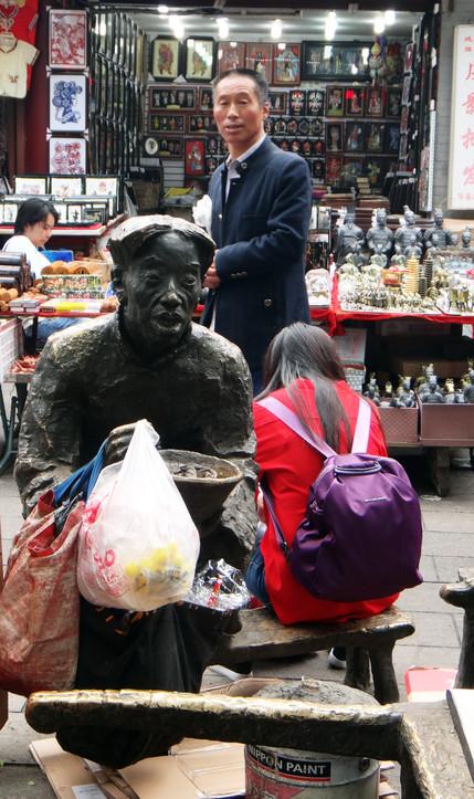 Man behind a statue in Xi'An, 2017.