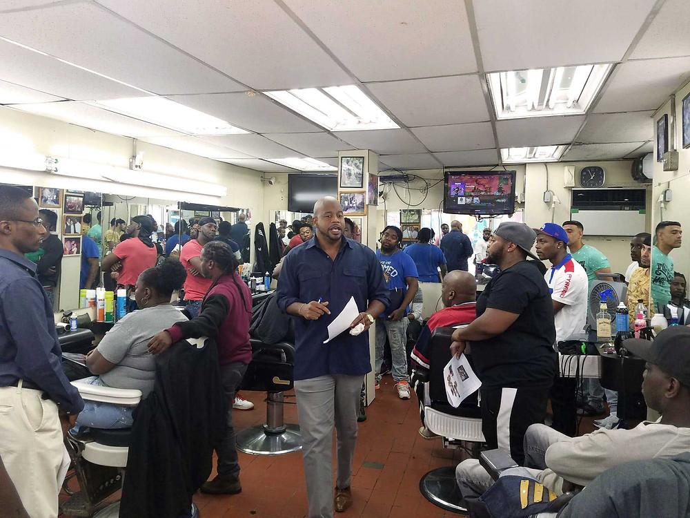 (Center )Matthew Morales, NYC Dept. of Health & Mental Hygiene at Hair Creations Barbershop in Brownsville Brooklyn.