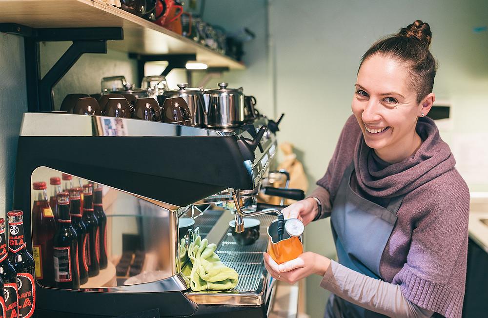 """Už baro besišypsanti Irina atvyko iš Kijevo, Ukrainos, ir yra vieno iš """"Dadada"""" dizainerių žmona. Ji bendrauja anglų, rusų kalbomis, sparčiai mokosi lietuvių. Kaip pasakoja Simona, dalis klientų į kavinę užsuka tik dėl Irinos: """"Kokia kavinė didelė ar maža bebūtų, barista yra jos veidas"""" (Valerijos Stonytės nuotr.)."""