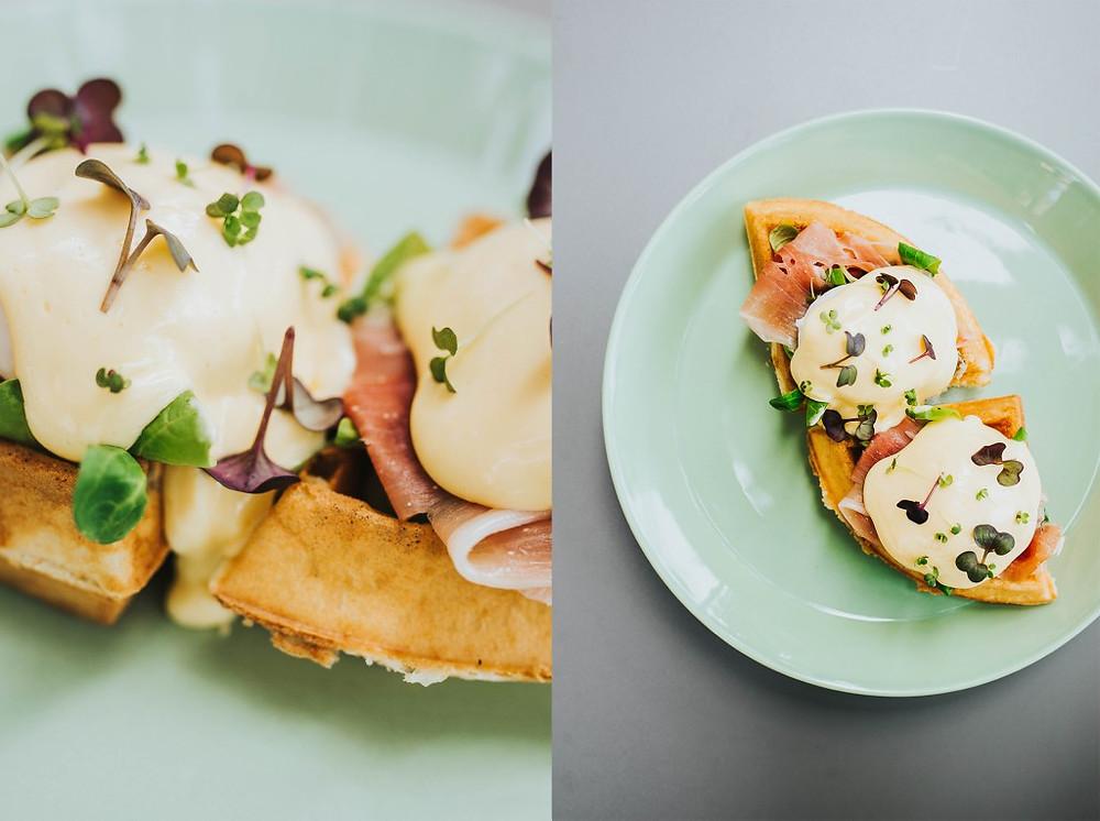 """Benedikto kiaušiniai, patiekiami ant belgiško vaflio, su salotomis, trumų aliejumi ir virtu itališku """"cotta"""" kumpiu. (Valerijos Stonytės nuotr.)"""