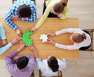 077440737-people-assembling-jigsaw-puzzl