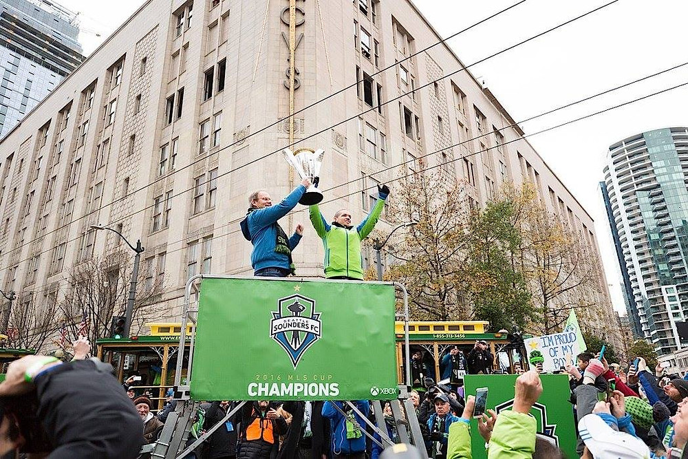 Head coach Brian Schmetzer and captain Osvaldo Alonso lift the trophy at the Sounders victory parade | Sounders FC Facebook
