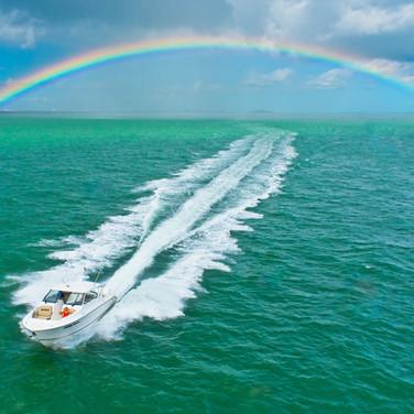 Pursuit boat driving through rainbow