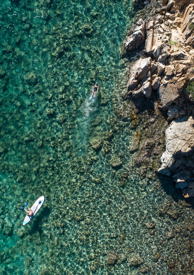 Drone image of people snorkling along shoreline.