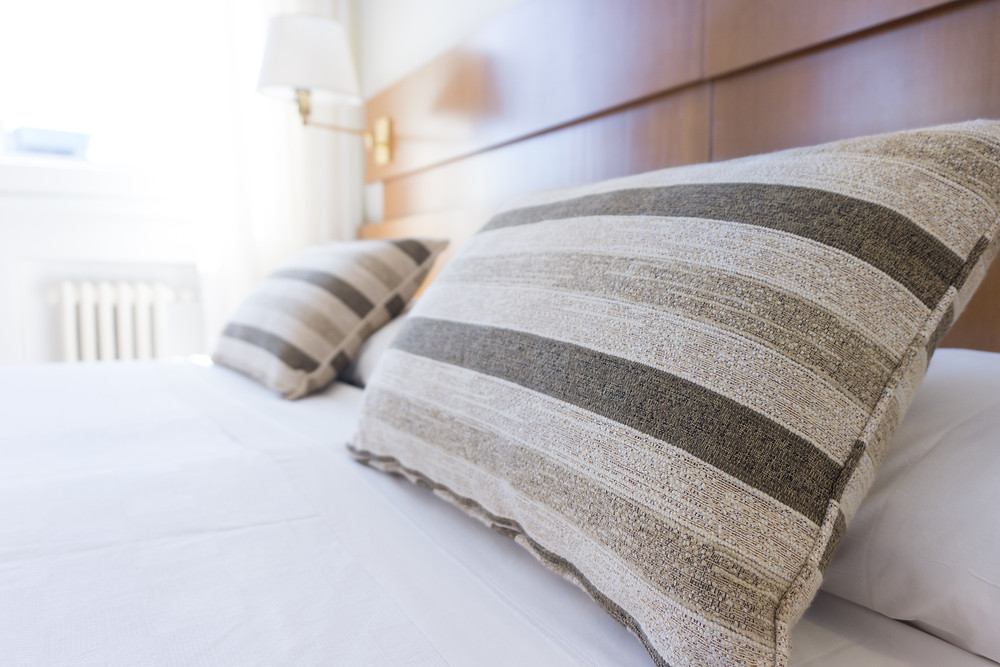 Grey striped pillows on a comfortable bed with white sheets in a vacation rental