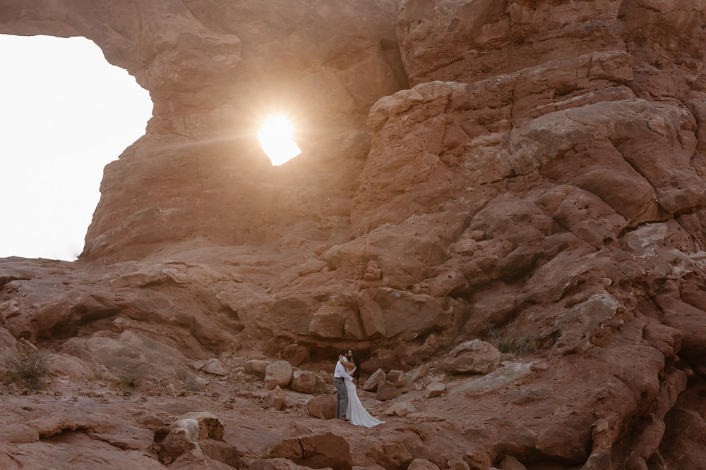 The sun peeks through a large hole in the red rocks of Arches National Park with a couple embracing each other in their wedding clothes