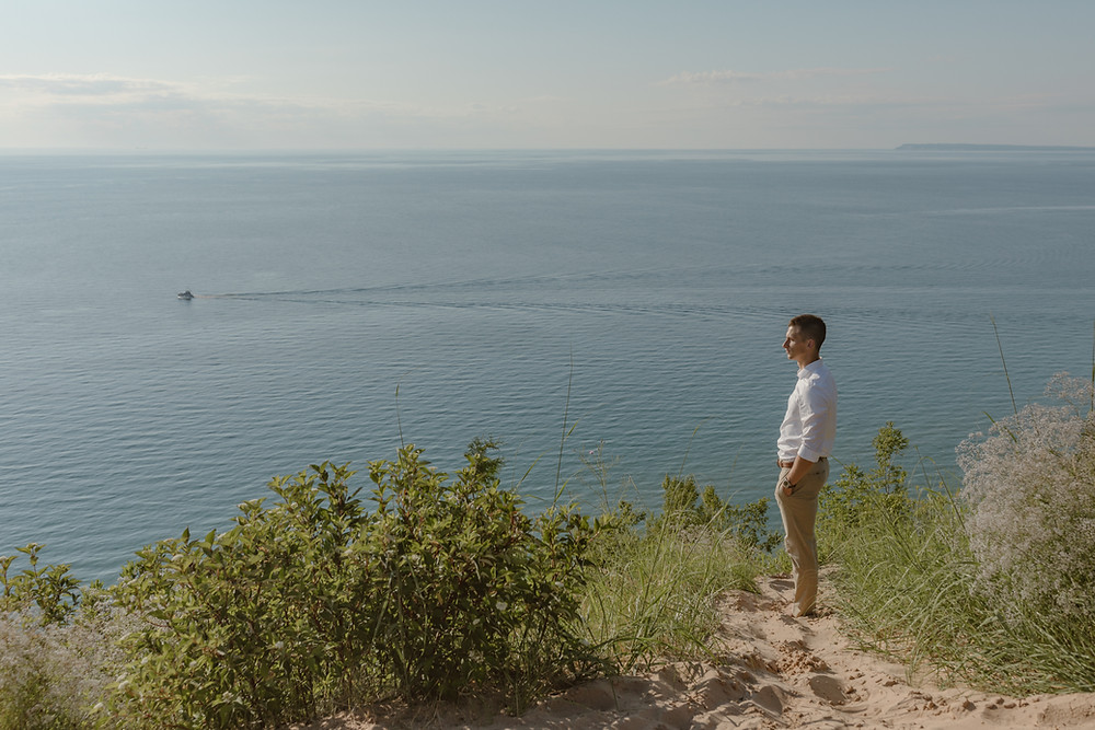 groom gazing over the ocean with a boat in the background, groom wearing kaki's on his elopement in Michigan
