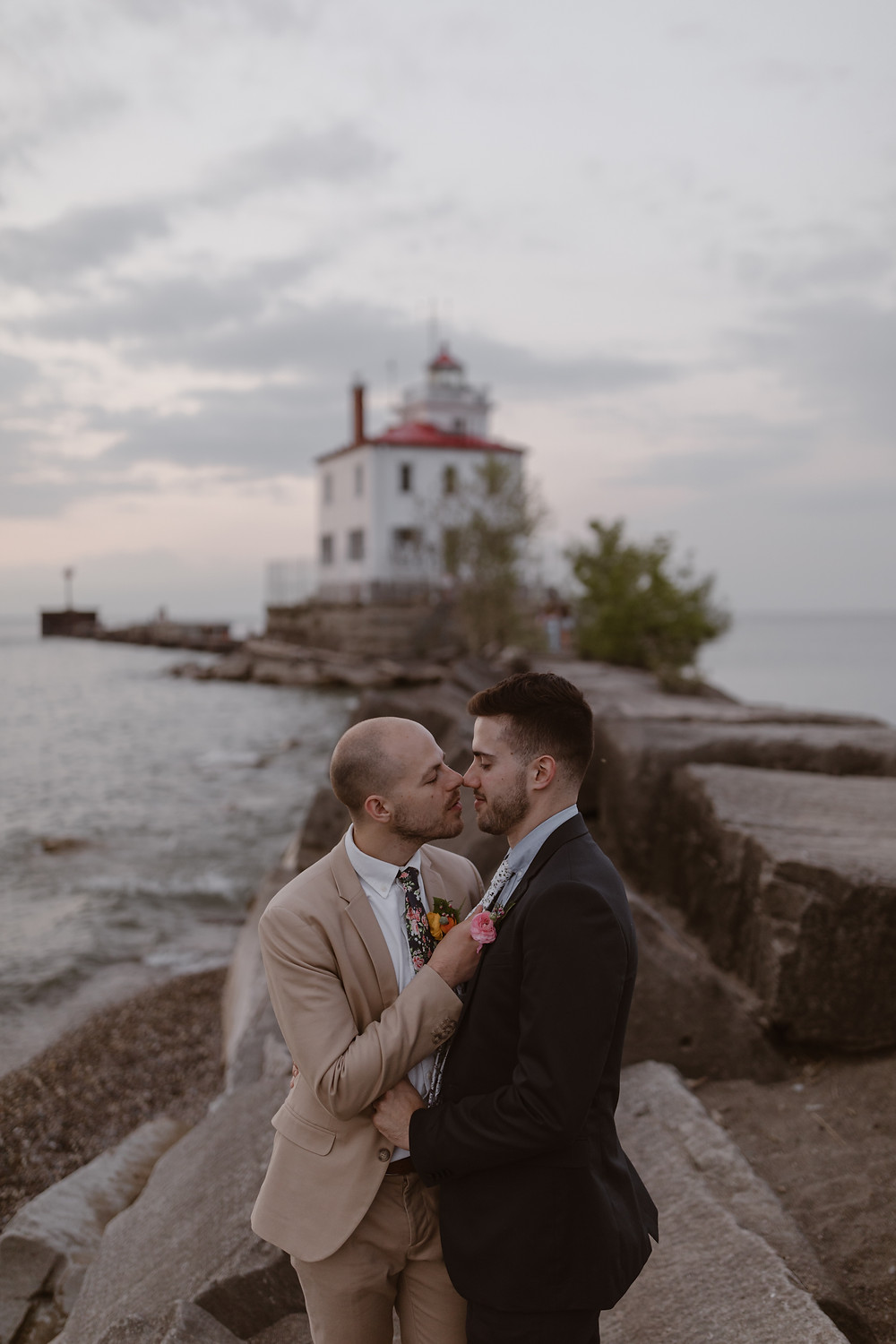 Cleveland Ohio elopement on Lake Erie a gay couple kissing infant of the lighthouse on headlands beach state park