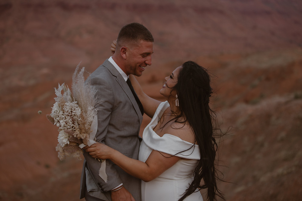 Eloping couple smiling and embracing each other on their Moab elopement day
