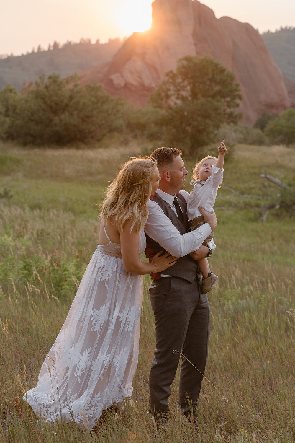 family elopement with red rocks and the sun setting behind them while the parents hold the baby