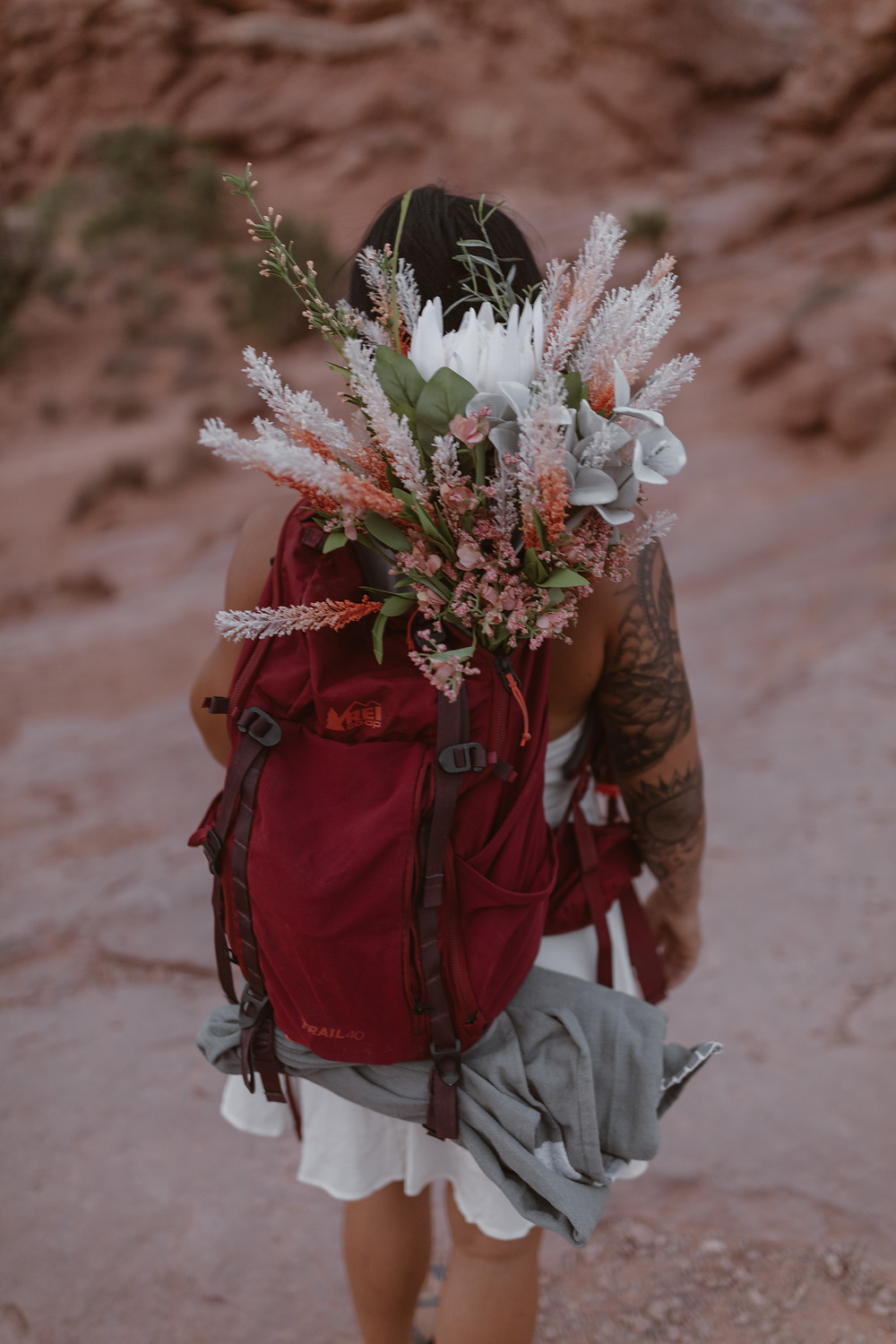 bride hiking with her bouquet in her hiking pack