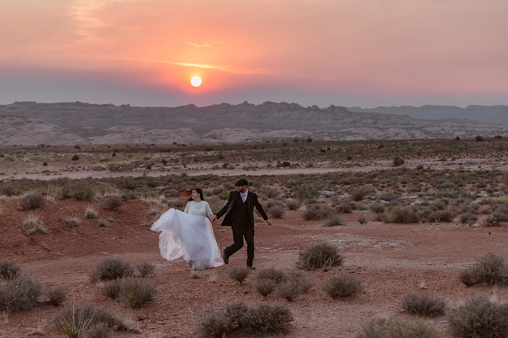 couple running in the desert of arches national park in their wedding attire on their elopement