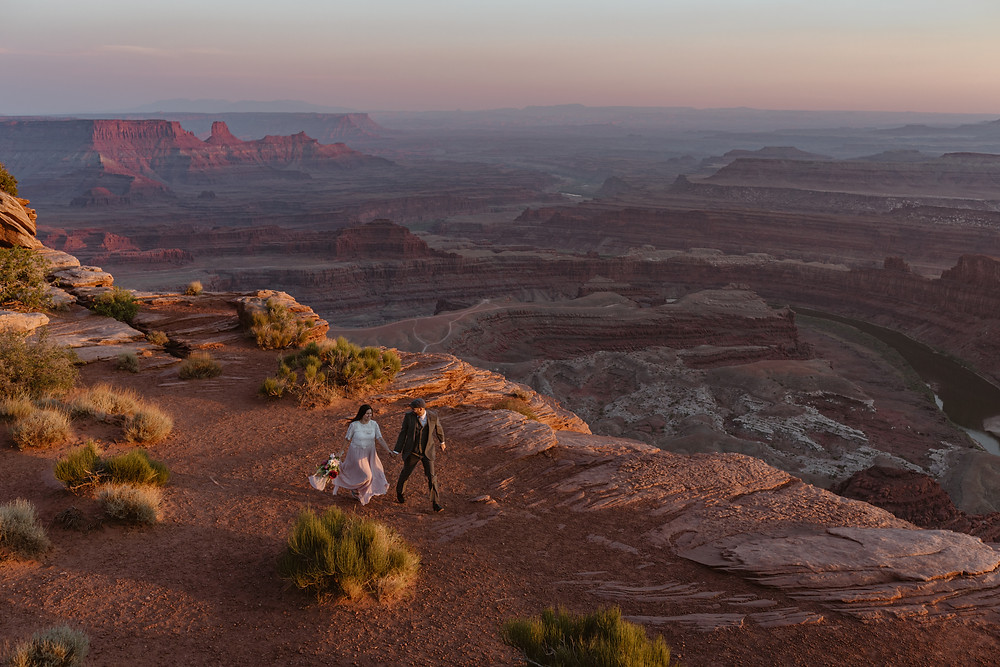 bride in dusty pink wedding dress and groom in tux running on the cliff of their dead horse point elopement in Moab Utah