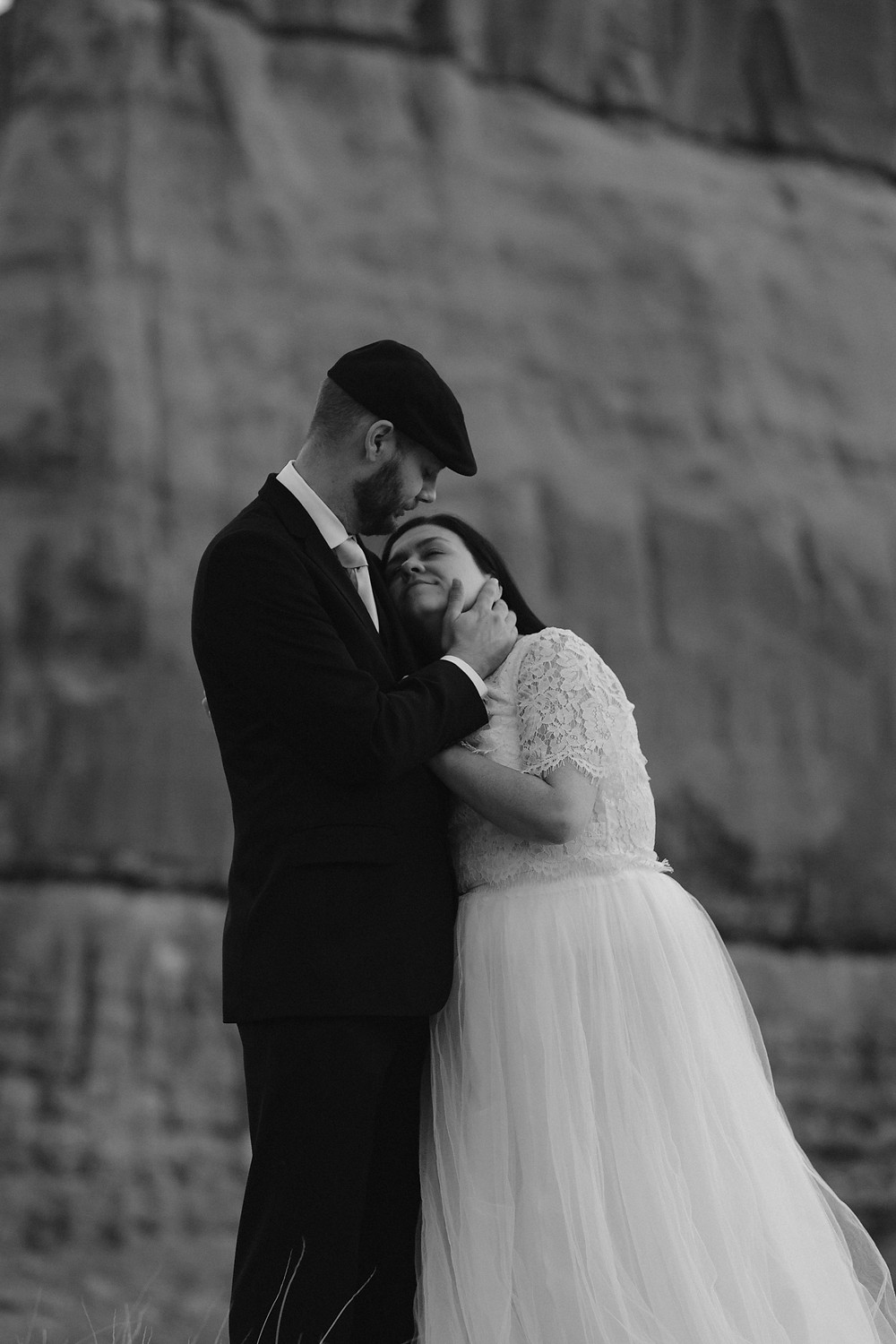 bride resting her head on her husbands chest while he caresses her cheek and look down at her