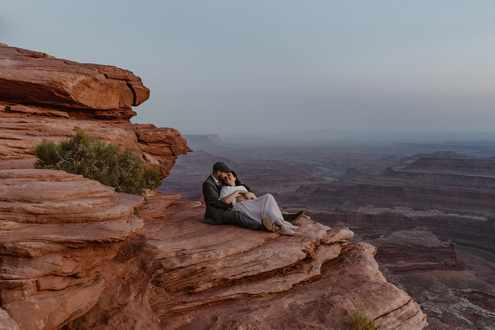 couple snuggling on a cliff at dead horse point state park on their wedding day