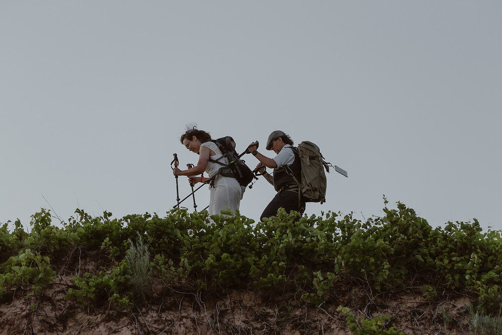 lesbian couple hiking on their elopement
