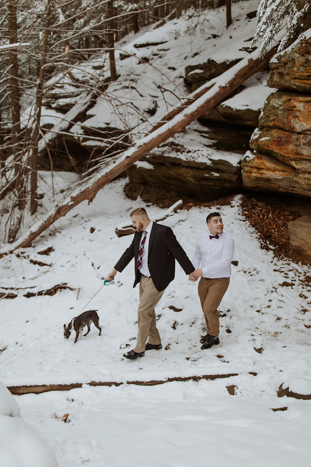 gay couple walking through the snow with their dog surrounded by ledges in the cuyahoga valley national park on their Ohio elopement
