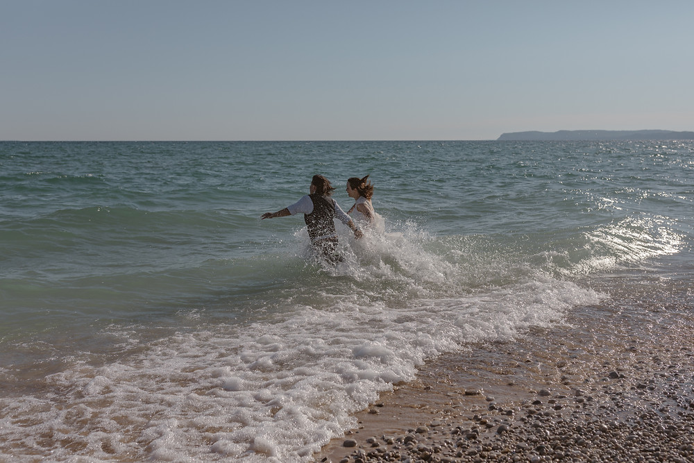 eloping LGBTQ couple running into Lake Michigan on their elopement day