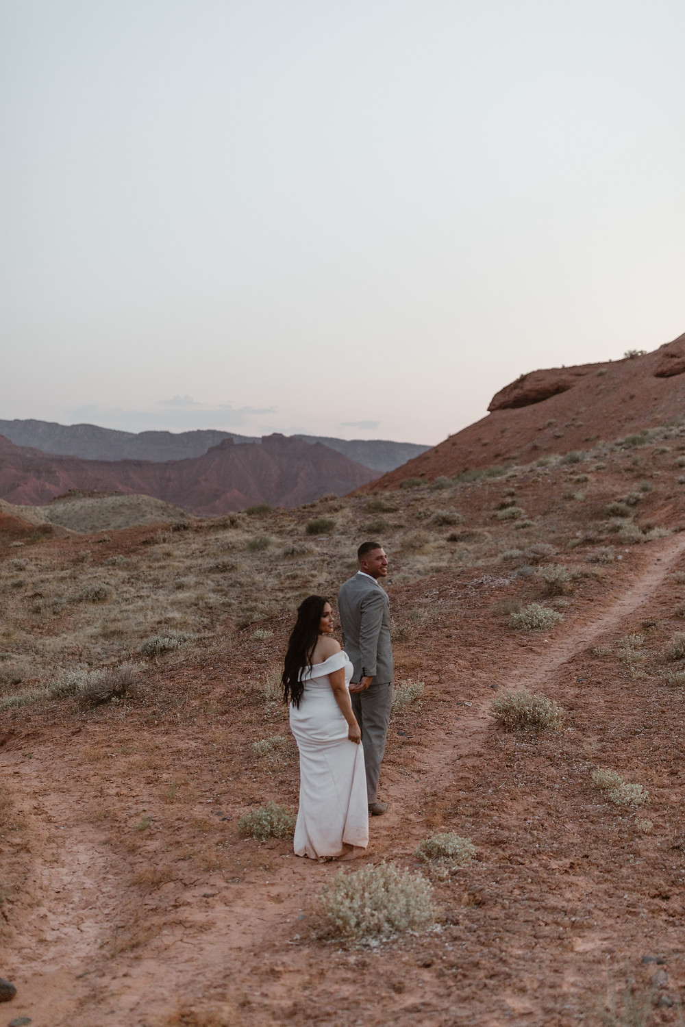 bride and groom walking on a trail in Moab