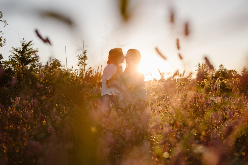 lesbian couple kissing at sunset in a wildflower field in Cleveland Ohio
