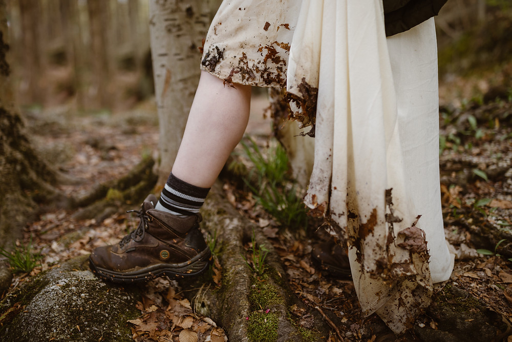 A bride wearing hiking boots and a very dirty wedding dress on her Nelson Kennedy Ledges wedding day